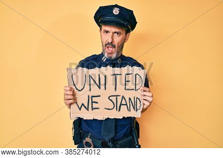 Middle age hispanic man wearing police uniform holding united we stand banner in shock face, looking skeptical and sarcastic, surprised with open mouth