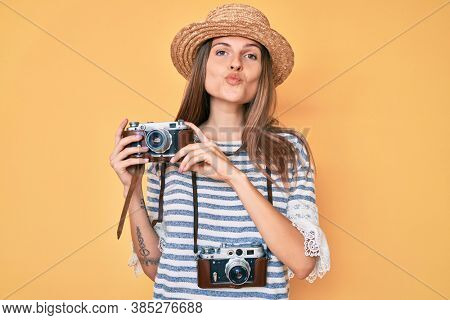 Beautiful caucasian tourist woman holding vintage camera looking at the camera blowing a kiss being lovely and sexy. love expression.