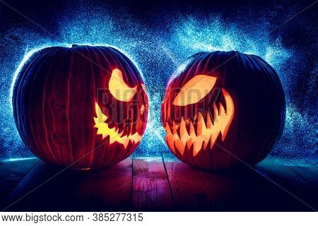 halloween pumpkins facing each other on black with dot lights in the background.