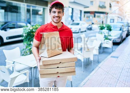 Young caucasian delivery man smiling happy holding  take away pizza cardboard walking at city.