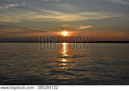 Hazy Golden Sunset Against A Bright Blue Cloudscape Reflecting Across The Calm Waters