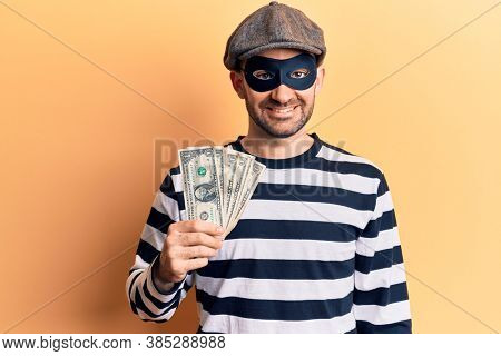 Young handsome man wearing burglar mask stealing dollars banknotes looking positive and happy standing and smiling with a confident smile showing teeth