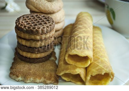 Waffle Rolls And Cookies On A White Plate And A Cup Of Tea. Waffles On The Side. Composition On A Wo