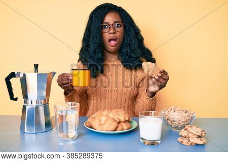 Young african american woman eating breakfast holding croissant in shock face, looking skeptical and sarcastic, surprised with open mouth