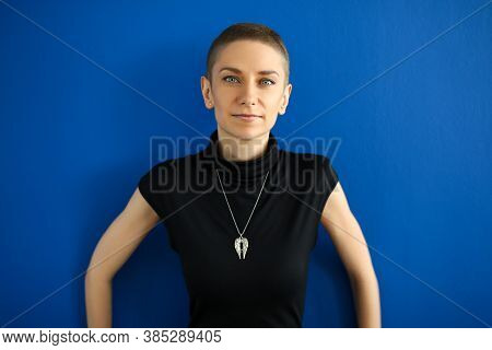 Portrait Of Stylish Beautiful Young Woman Posing On Blue Wall. Good-looking Female In Black Top. Pre