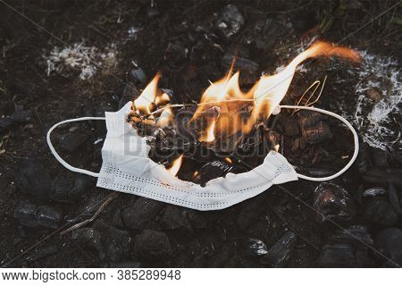 Burning A Medical Mask, Surgical Mask With Cleansing Decontaminate Fire. Concept Of End Of Coronavir