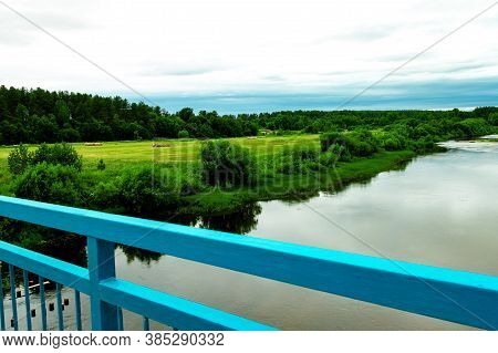 View Of River And Fields With Haystacks, Trees And Nature Over The Railing Of The Old Blue Bridge. S
