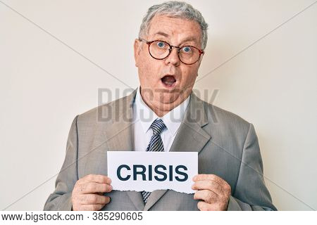 Senior grey-haired man wearing business suit holding crisis paper in shock face, looking skeptical and sarcastic, surprised with open mouth