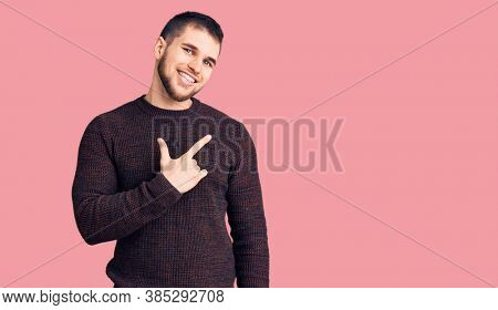 Young handsome man wearing casual sweater cheerful with a smile of face pointing with hand and finger up to the side with happy and natural expression on face