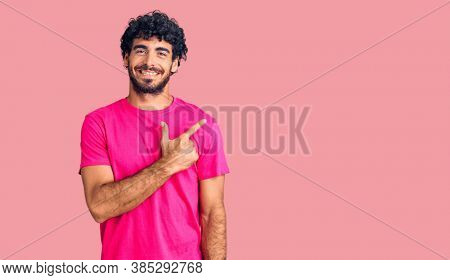 Handsome young man with curly hair and bear wearing casual pink tshirt cheerful with a smile of face pointing with hand and finger up to the side with happy and natural expression on face