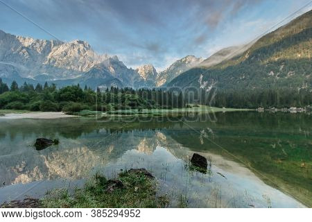 Mirror Reflection In Lago Di Fusine, Italy. Summer Spring Colors And Mangart Mountain In The Backgro