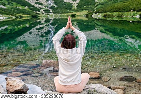 Young Woman In A White Hoodie Practicing Yoga On A Lake Shore With Transparent Water With An Amazing