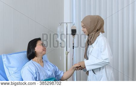 Muslim Female Doctor Holding Hand Of The Elderly Patient Sitting On The Bed At Hospital, Takes Care