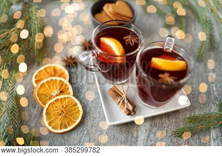 christmas and seasonal drinks concept - hot mulled wine, dry orange slices, gingerbread and aromatic spices on grey background