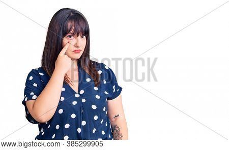 Young plus size woman wearing casual clothes pointing to the eye watching you gesture, suspicious expression