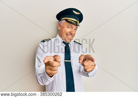 Handsome middle age mature man wearing airplane pilot uniform pointing fingers to camera with happy and funny face. good energy and vibes.