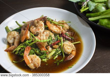 Fried Water Mimosa With Shrimp And Oyster Sauce In White Plate On Wooden Table