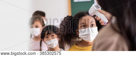 Teacher Using Digital Thermometer For Check Temperature Measurement On African American Girls Forehe