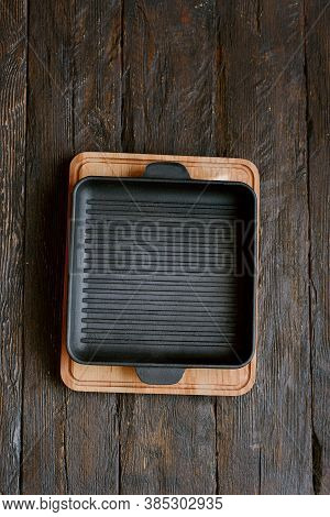 New Empty Cast-iron Grill Pan With Two Handles On Wooden Background. Place For Text. Flat Lay Top Vi
