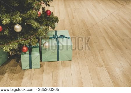 Christmas Tree With Decorations And Presents Under It Interior. Blue Box On The Floor Under The Chri