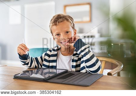 Child drawing picture with digital pen on tablet while looking at camera. Portrait of smiling cute kid using stylus on tablet to do homework for school. Artistic boy drawing on digital tablet at home.