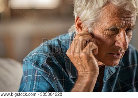 Senior man holding ears while suffering from pain. Tensed mature man holding ears. Side view of senior man with symptom of hearing loss, copy space. Retired man with fingers near ear suffering pain.