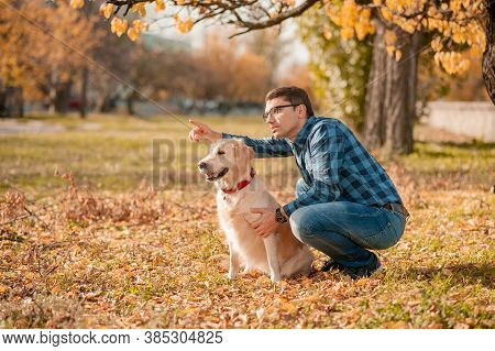 Portrait Of Young Man Sitting Hugging With Golden Retriever Dog. Friendship, Pet And Human. Man Play