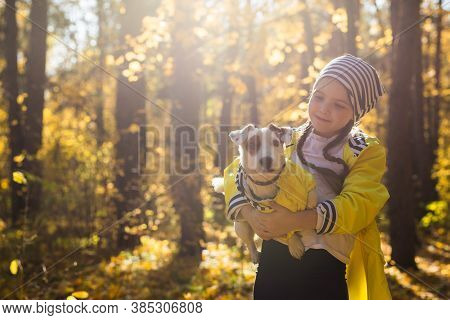 Portrait Of A Little Girl On A Background Of Orange And Yellow Leaves In An Autumnal Sunny Day. Litt