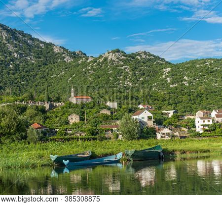 View From The River To The City Dodosi. In The Foreground A Boat. With Reflection. Skadar (shkoder)