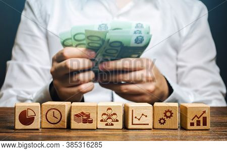 A Man Is Counting Money And Blocks With Business Attributes. Good Business Model. Profitability. The