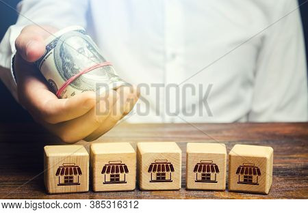Blocks Symbolizing Business Network And Businessman Holds Out Money. Offer For Purchase Of A Busines