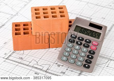 Calculator With Bricks On Architectural House Building Blueprint Plan Background, Real Estate Or Hou