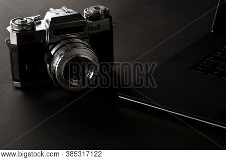 Retro Analog Slr Camera Next To Laptop On Black Desk In Office, Digital Photography Or Image Process
