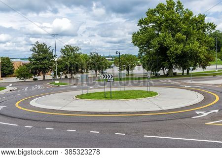 Horizontal Shot Of A Traffic Roundabout Near A Suburban Mall.