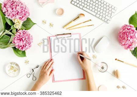 Female Workspace With Female Hands, Clipboard, Bouquet Hydrangea, Computer, Accessories On White Bac