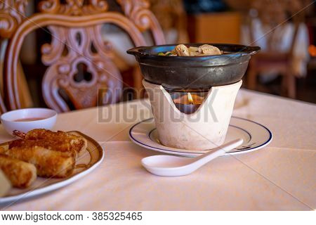 Fried Spring Rolls And Hot Thai Soup Served On A White Stand On A Candle Fire. Delicious Lunch In As