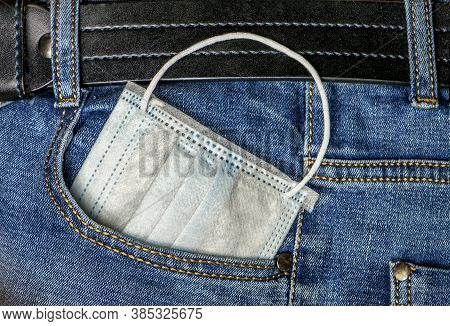 Protective Medical Mask Is Sticking Out Of The Jeans Pocket. Carry The Mask With You In Your Jeans P