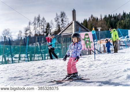 Young happy skier girl learning how to ski on the green ski zone. Young skier having fun on ski slope, Bialka Tatrzanska, Tatry, Poland
