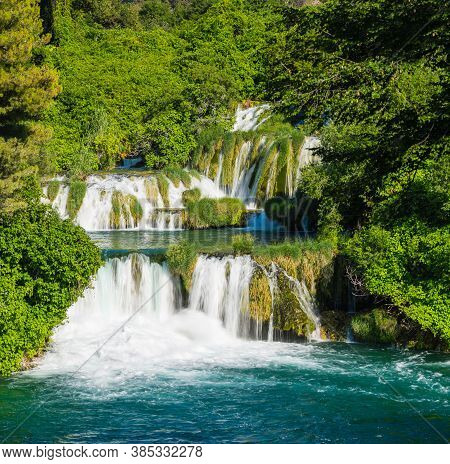 Cascade Waterfalls Surrounded By Dense Forest. Sunny Day. Krka National Park, Croatia.
