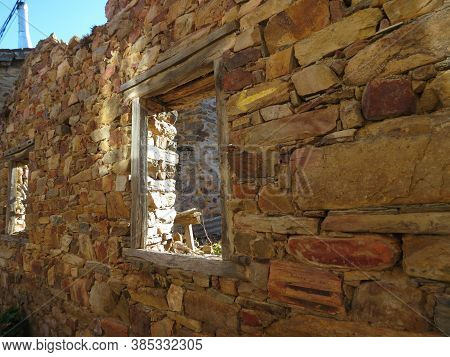 Ruins Of A Country House In Northern Spain - Shade Outside Of A Rough Stone Wall And Window Showing