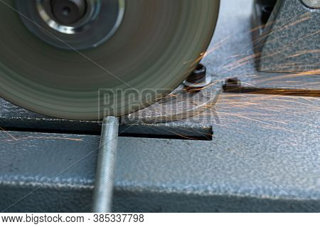 The Angle Grinder Cuts The Metal Pin. The Angle Grinder Is Mounted On A Stand. Sparks Fly From Under