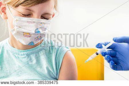 Little Girl In Face Mask In Doctor's Office Is Vaccinated.crying, Scared, Afraid Of Syringe With Vac