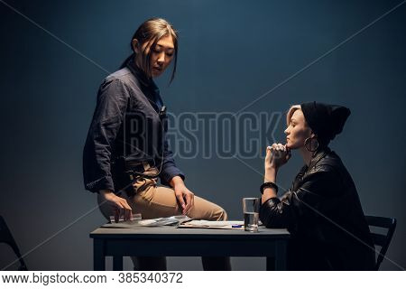 A Young Investigator An Asian Woman Sits On A Table During The Interrogation Of A Pretty Criminal.