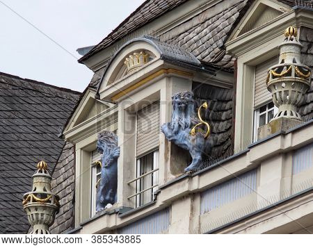 Figures Of Blue Lions With Gold Tails Holding A Dormer Window With A Crown On Top. Building In Main