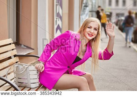 Smiling Mature Woman In Pink Cloth Is Sitting On The Bench On The Crowded City Street And Waving A H