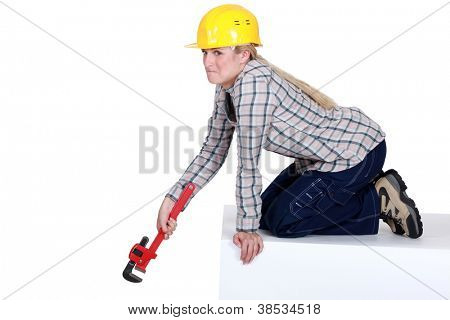Unhappy tradeswoman holding a pipe wrench