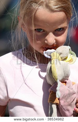 Little girl with a pacifier and a dirty toy bunny