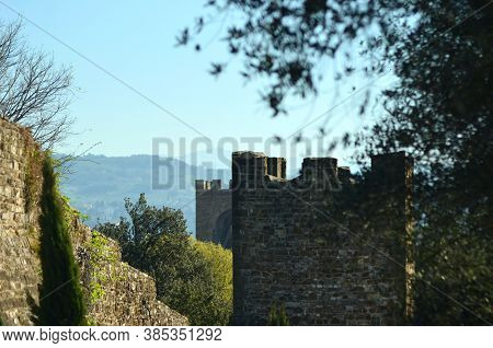 Two Turrets And Part Of The Old Wall Once Surrounding Florence. Hills Are In The Distance, And The S