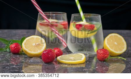 Fresh Strawberries And Lemon Slices On The Background Of Two Glasses With A Cooling Drink. Selective