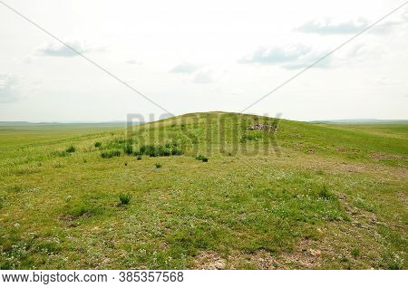 A High Hill Along The Endless Steppe Covered With Green Grass.